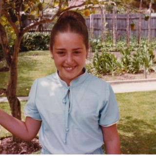 My amazing Mum had put my hair up in an onion which I loved. Here I am posing against our awesome Nespoli tree with our garden in the background. It's October, 1980.
