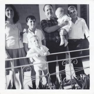 A precious photo Mum took of Dad holding baby Jimmy, with Ellen, Sam, Frank and Nick surrounding him.