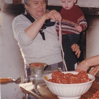 In 1998, we lived with Mum and this photo shows her happily teaching Sam the secrets of sausage making.
