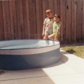 Jim and Nick leaning against their swimming pool that Dad had bought them.
